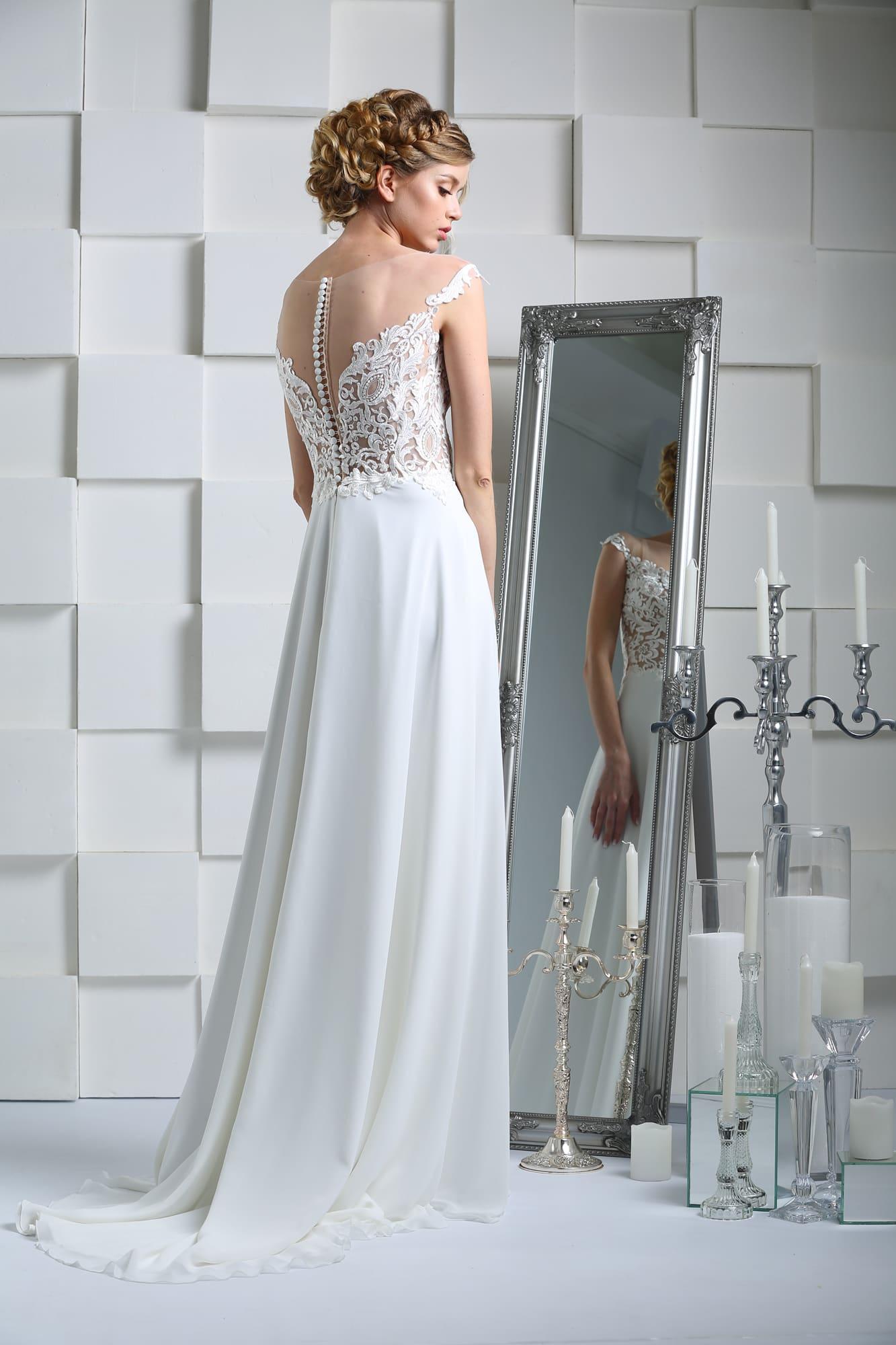 Прямое свадебное платье с выразительным декольте, открытой спинкой и небольшим шлейфом.