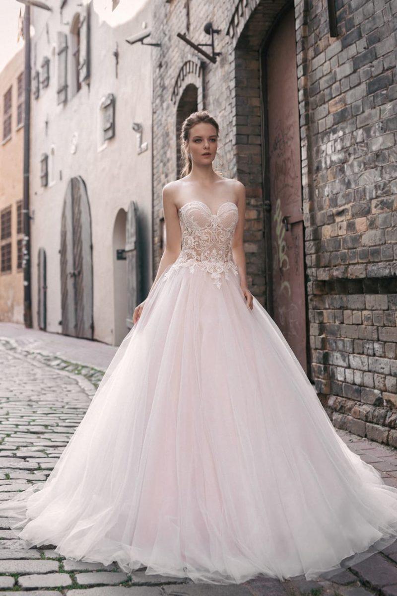 Открытое свадебное платье «принцесса» на пудровой подкладке, украшенное кружевом.