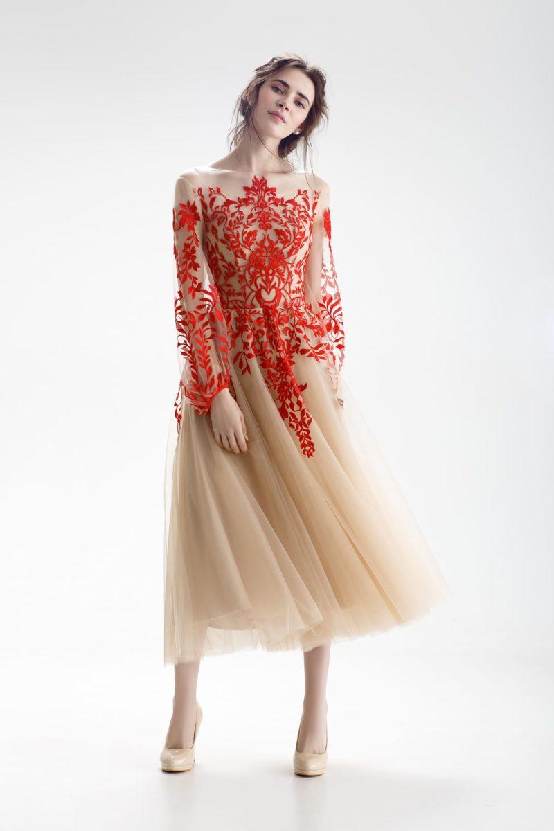 Свадебное платье бежевого цвета с алой отделкой и длинным объемным рукавом.