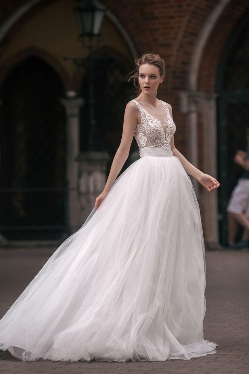 Свадебное платье А-силуэта с глубокими вырезами на лифе и спинке и кружевным декором.