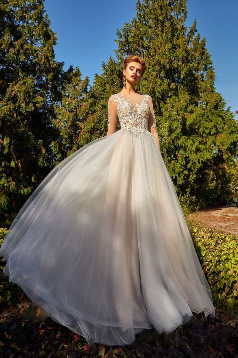 Вечернее платье в пудровых тонах с длинным прозрачным рукавом и кружевным декором.