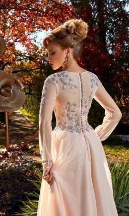 Пудровое вечернее платье с длинным рукавом широкого кроя и многослойным подолом.