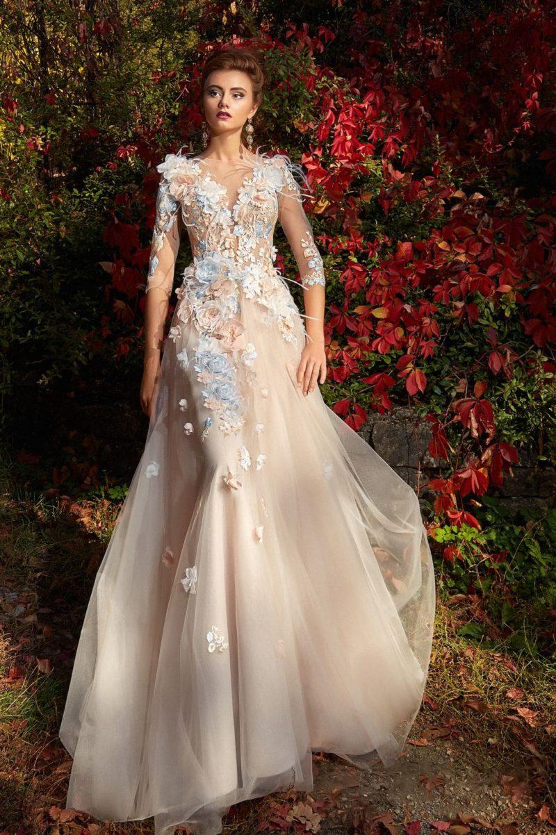 Бежевое вечернее платье с длинным полупрозрачным рукавом и объемной отделкой.