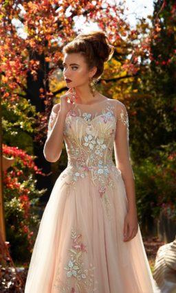 Бежевое вечернее платье с полупрозрачным рукавом и романтичной цветочной отделкой.