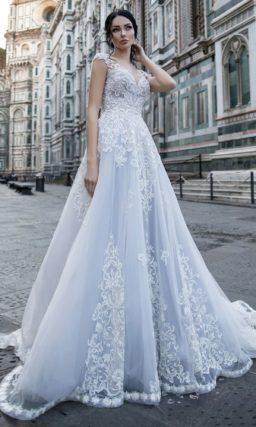 Роскошное свадебное платье с тонкой вставкой над лифом и кружевным декором.