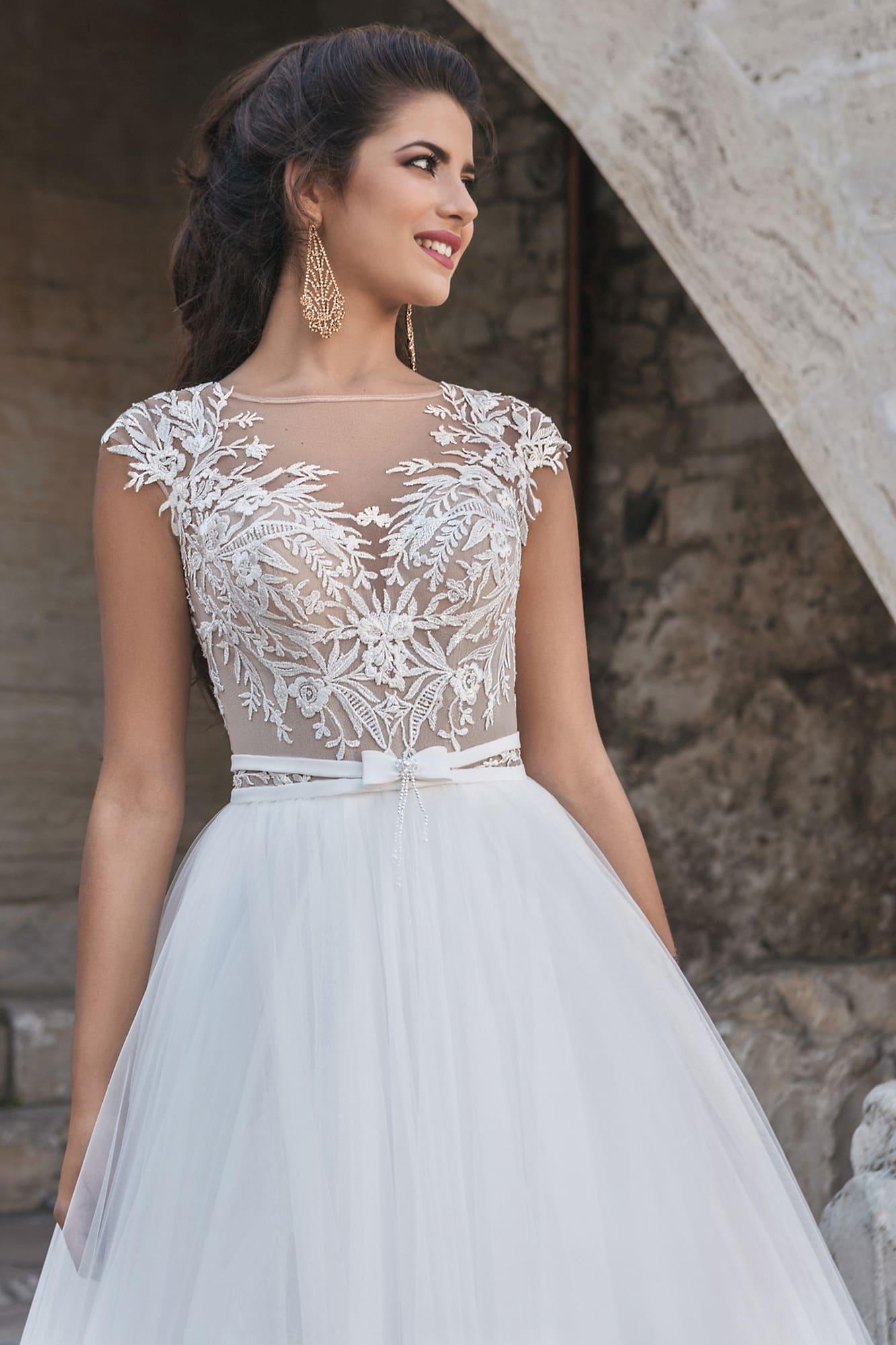 Романтичное свадебное платье с многослойной юбкой и полупрозрачным лифом без рукава.
