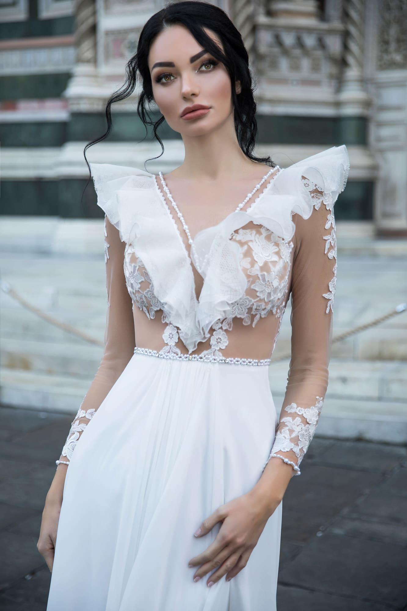 Прямое свадебное платье с объемными оборками по прозрачному верху с длинным рукавом.