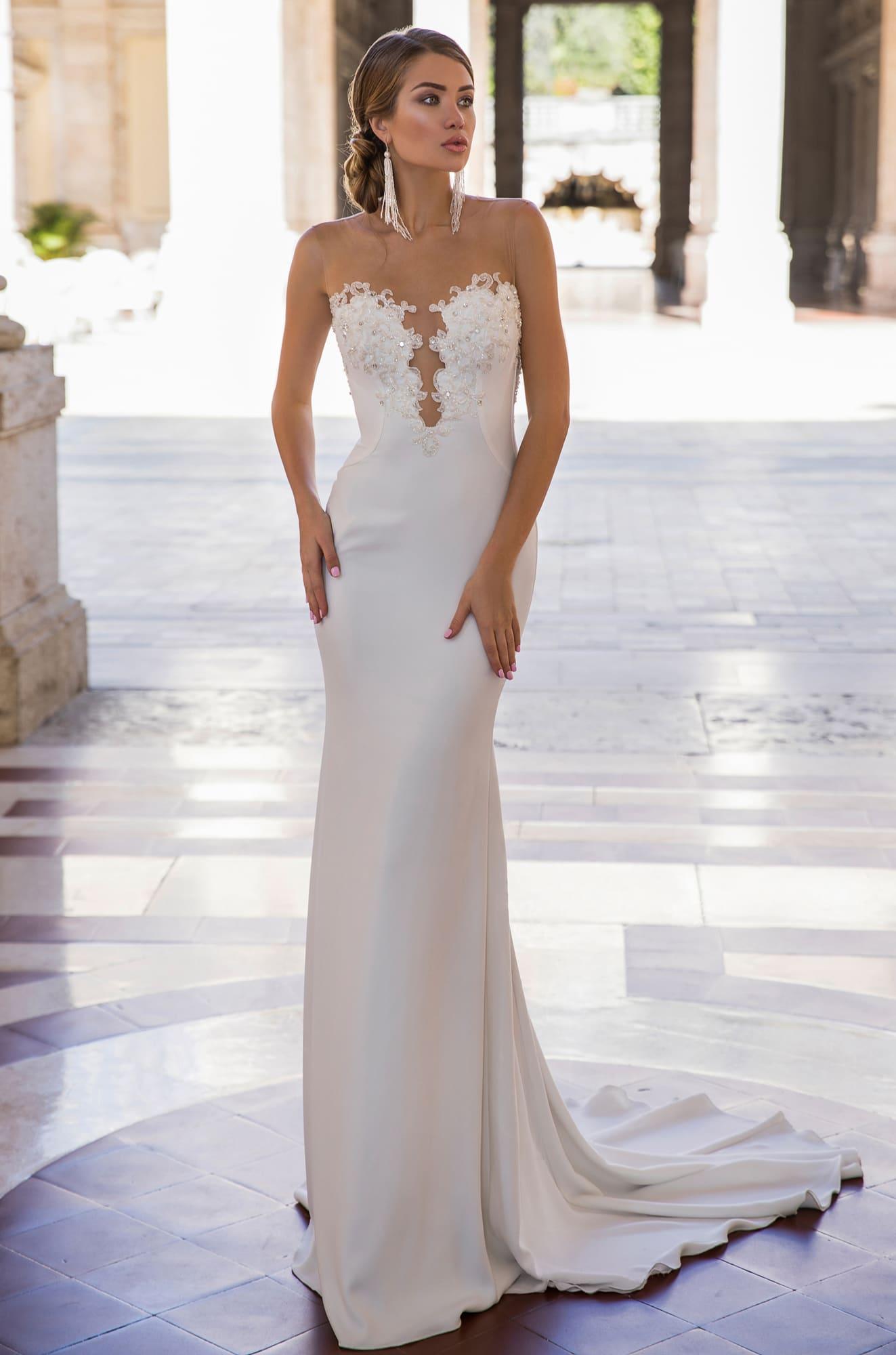 Облегающее свадебное платье с глубоким вырезом, украшенным по краю кружевом.