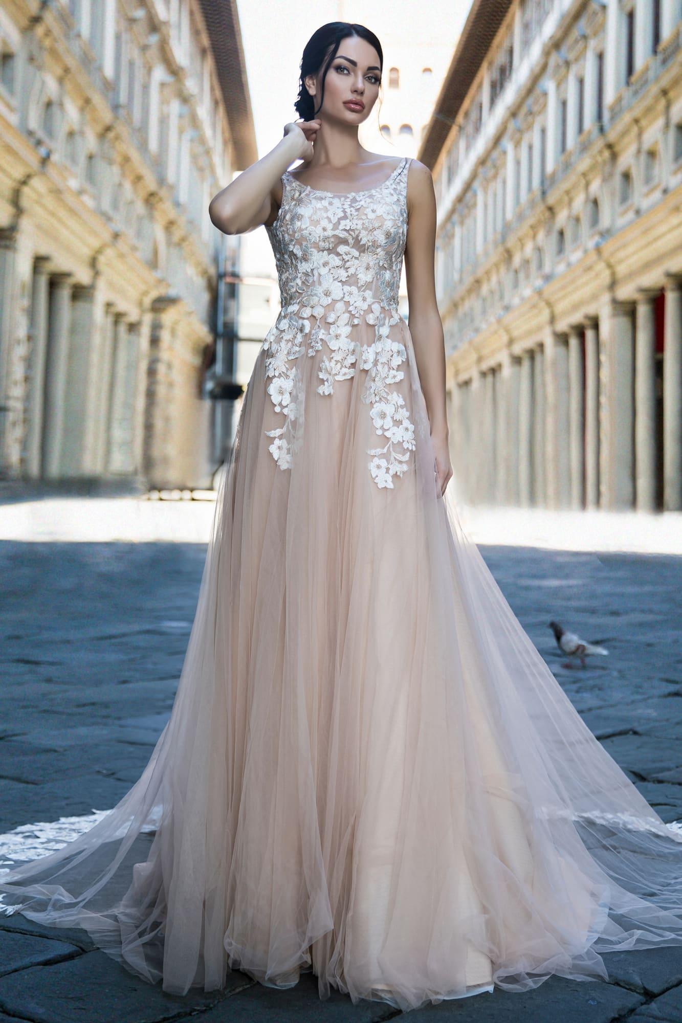 Прямое свадебное платье бежевого цвета, украшенное белыми кружевными аппликациями.