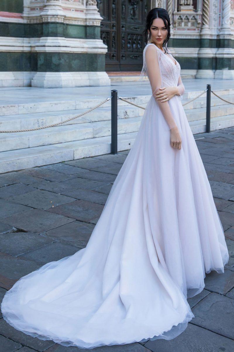 Нежное свадебное платье с элегантным открытым лифом и многослойной юбкой.