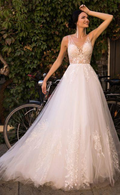 Элегантное свадебное платье с полупрозрачным лифом и пышной юбкой со шлейфом.