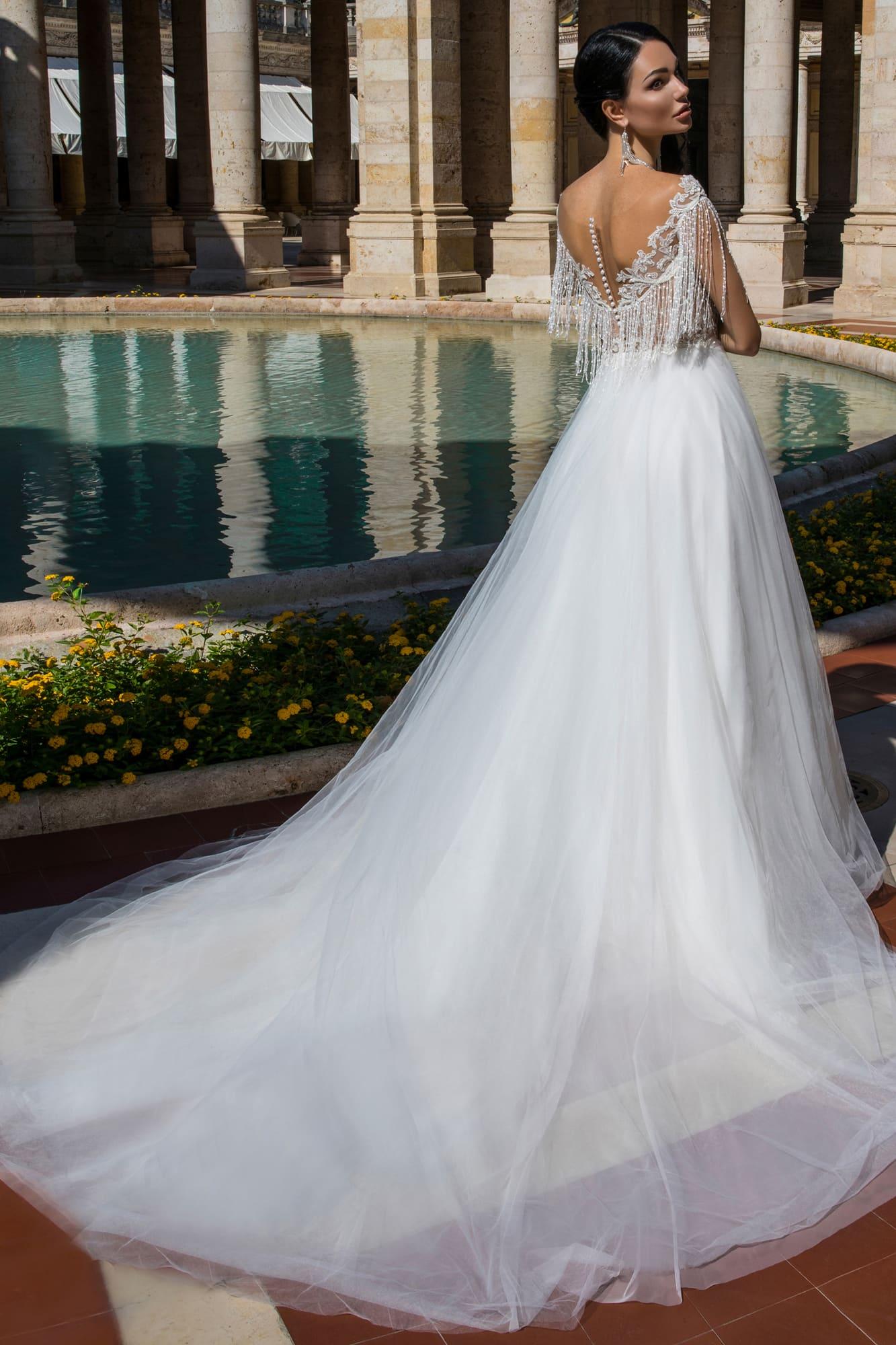 Воздушное свадебное платье с эффектным вырезом и сияющей отделкой верха.