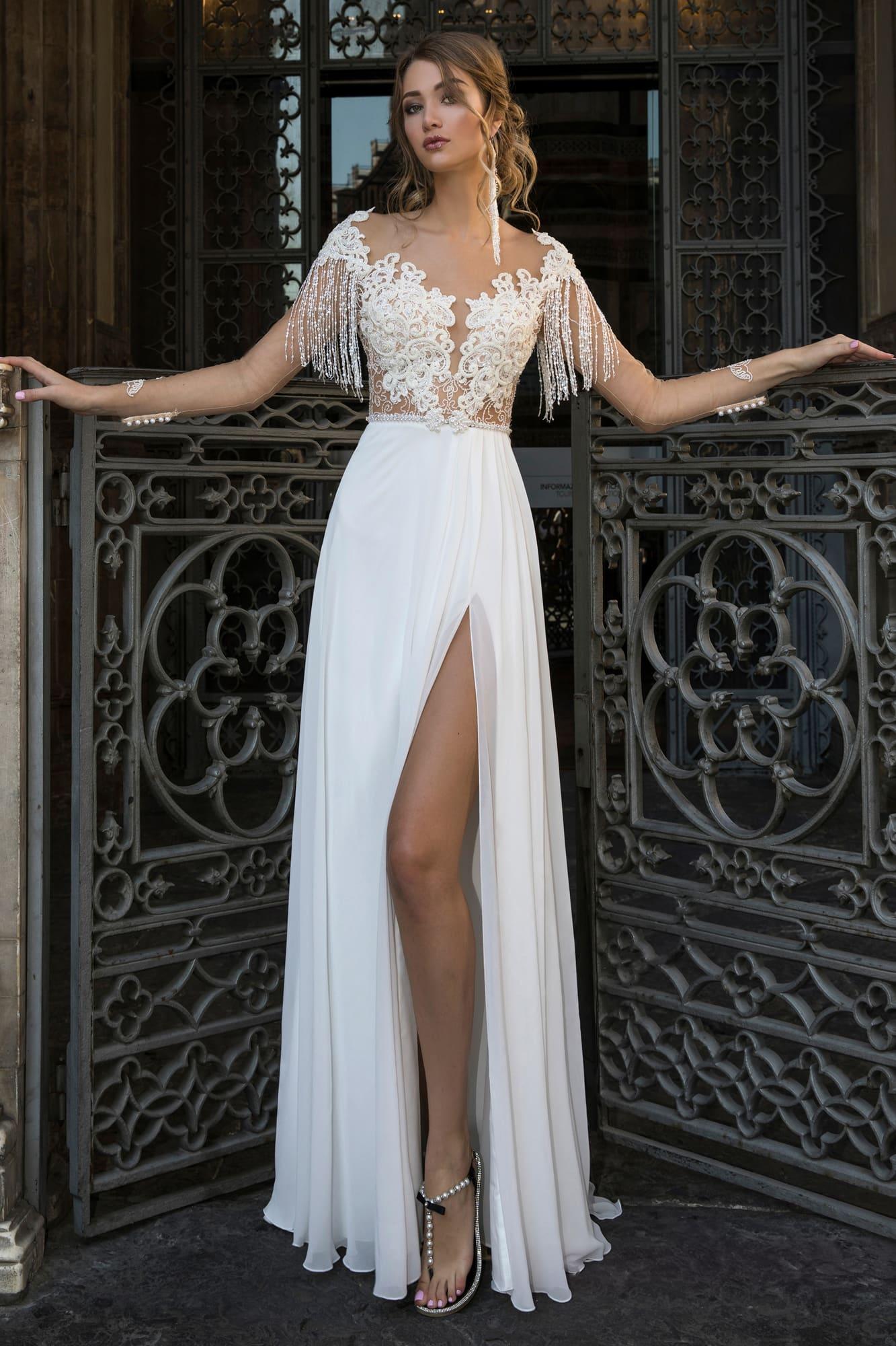 Прямое свадебное платье с соблазнительным разрезом по подолу и бахромой на лифе.