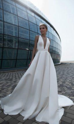 Минималистичное свадебное платье с глубоким декольте и пышным бантом на спинке.
