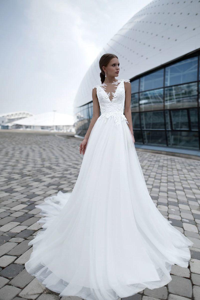 Роскошное свадебное платье с кружевными аппликациями и прозрачной спинкой.