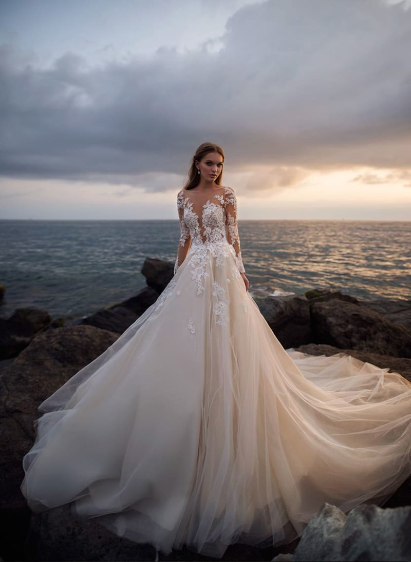 Свадебное платье персикового цвета с роскошным шлейфом и длинным рукавом.