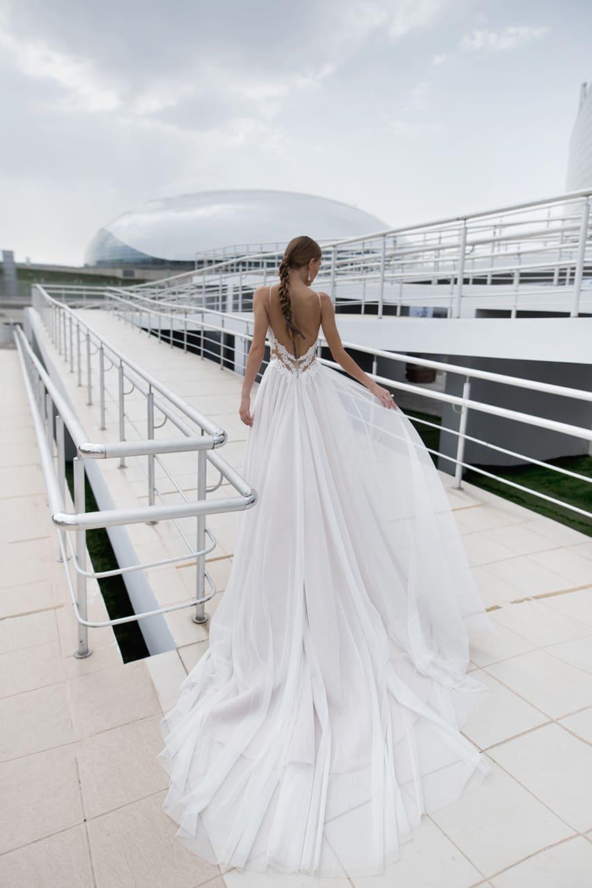 Нежное свадебное платье с открытым лифом на тонких бретелях, украшенным кружевом.