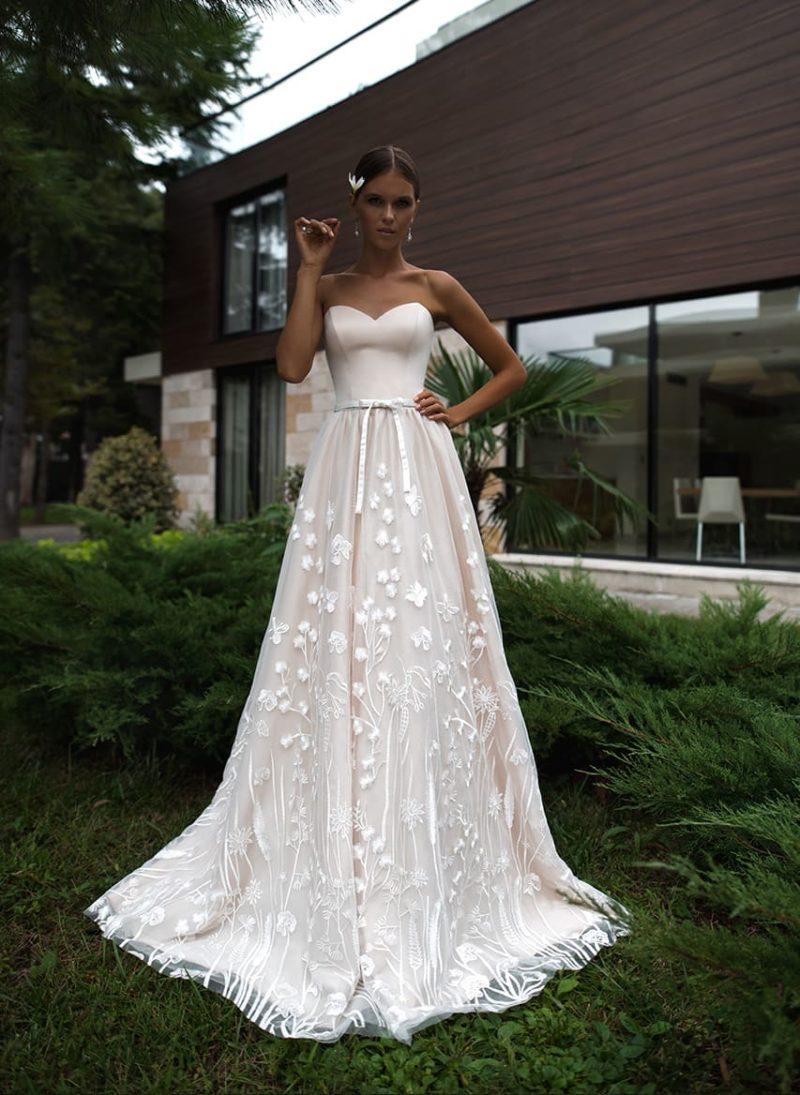 Свадебное платье персикового цвета с открытым верхом и цветочным декором.