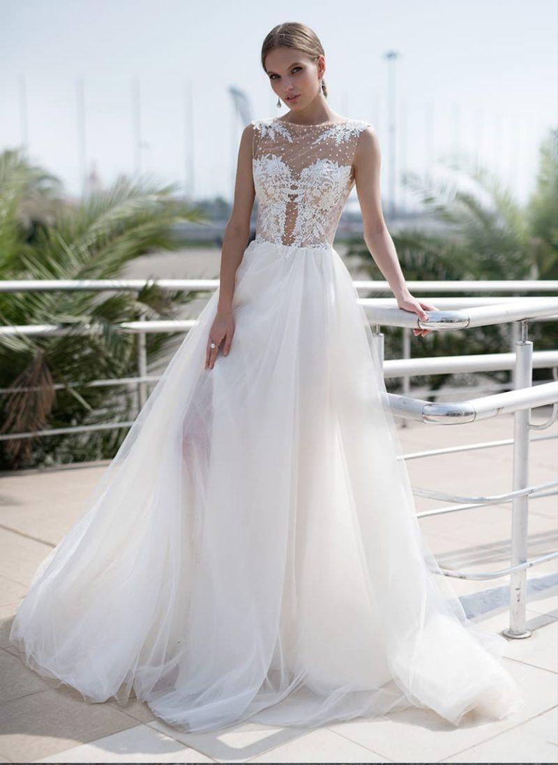 Прямое свадебное платье с тонким лифом с кружевом и юбкой из нескольких слоев ткани.