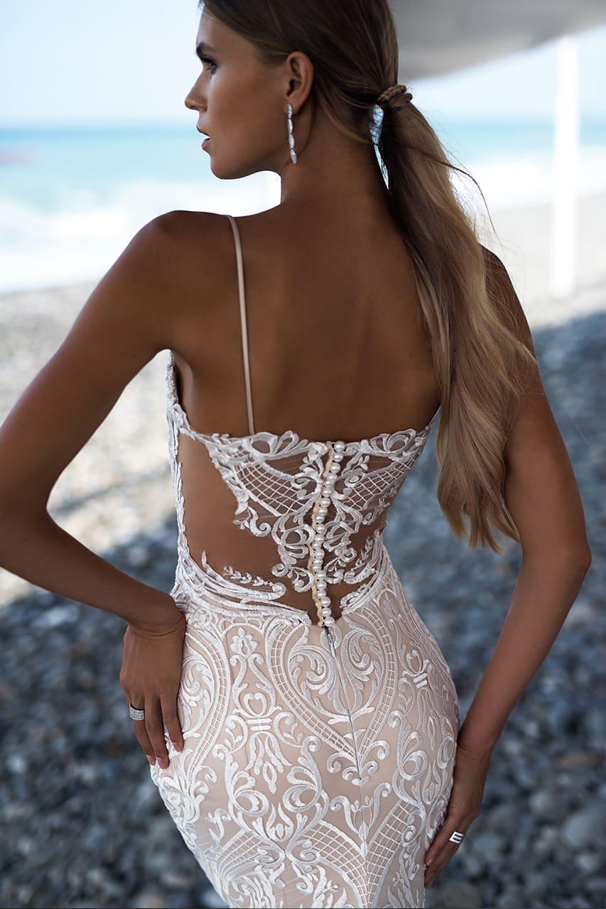 Облегающее свадебное платье с белой кружевной отделкой и пышным шлейфом.