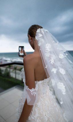 Свадебное платье с объемной отделкой и роскошной юбкой со шлейфом.
