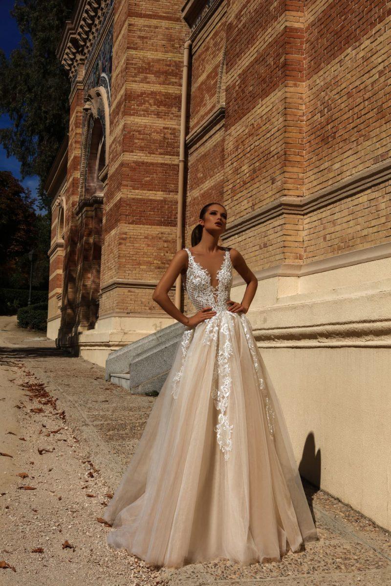 Кремовое свадебное платье с чарующим шлейфом и глубоким декольте.