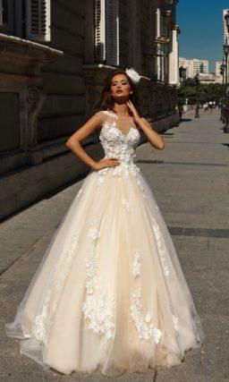Свадебное платье пышного силуэта с белыми аппликациями и кремовой юбкой.