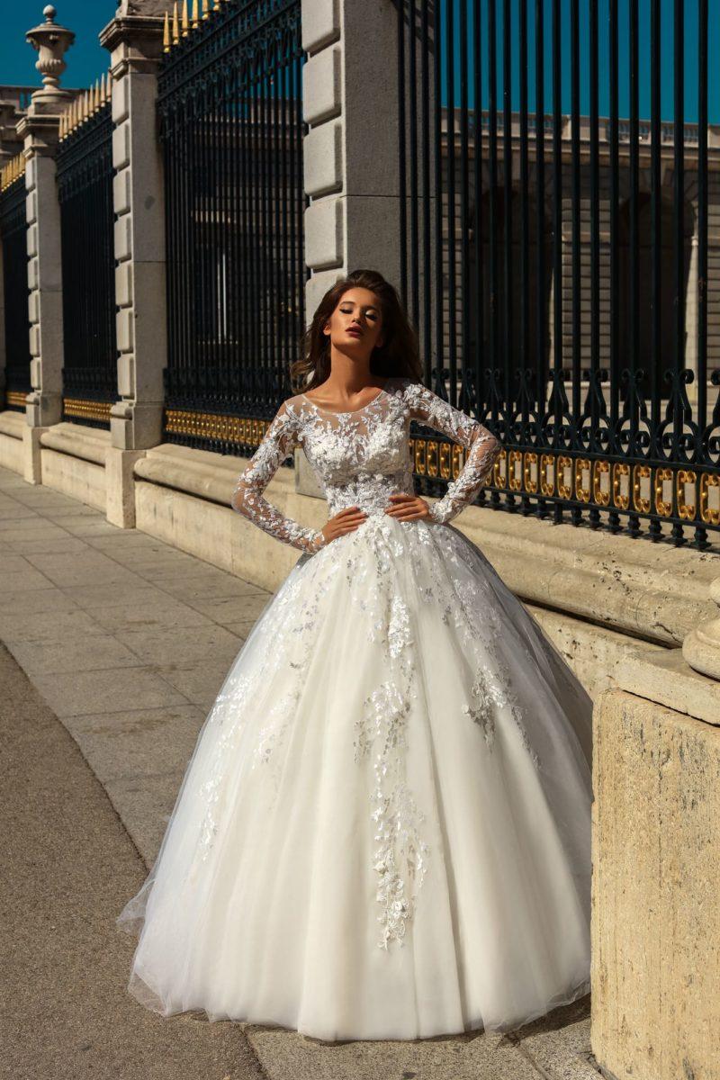 Пышное свадебное платье с длинным рукавом и кружевной отделкой верха.