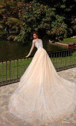 Пудровое свадебное платье с длинным рукавом и белой кружевной отделкой.