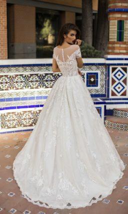 Пышное свадебное платье с полупрозрачным верхом и коротким рукавом.