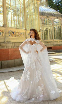 Свадебное платье с кружевным кейпом и многослойной юбкой со шлейфом сзади.