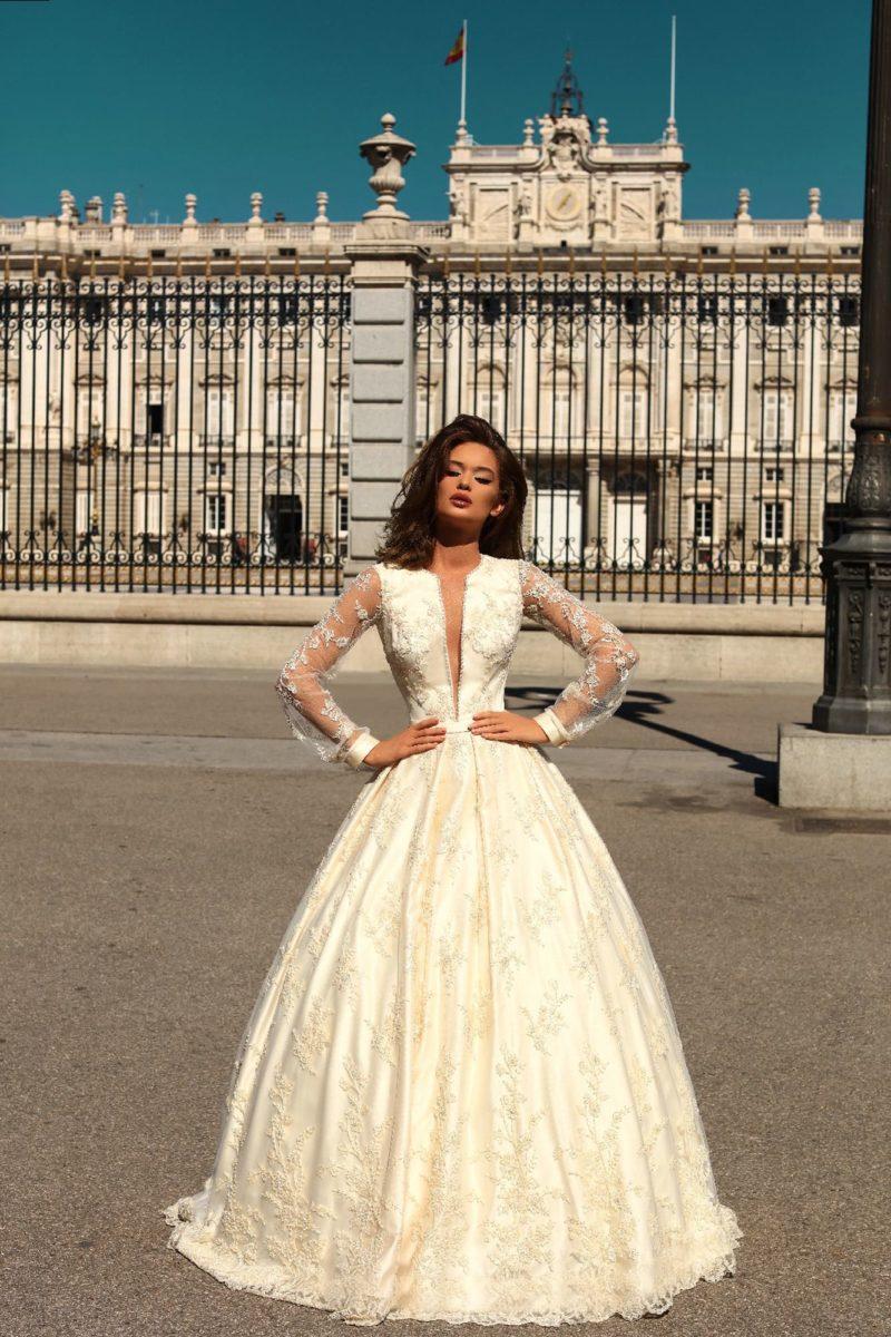 Пышное свадебное платье кремового цвета с длинным полупрозрачным рукавом.