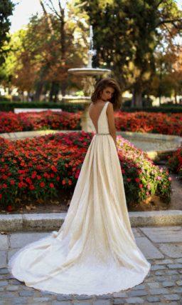 Золотистое свадебное платье с роскошными складками на юбке и глубоким вырезом.