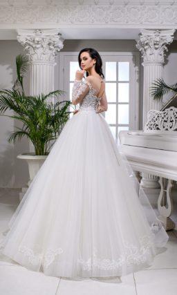 Пышное свадебное платье с отделкой аппликациями и прозрачным рукавом.