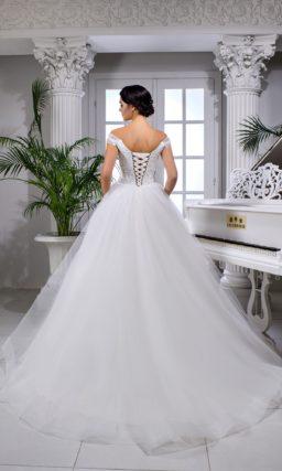 Свадебное платье с открытым верхом и бретелями на предплечьях.