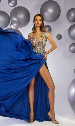 Прямое вечернее платье в пол с высоким разрезом на юбке и длинным рукавом.