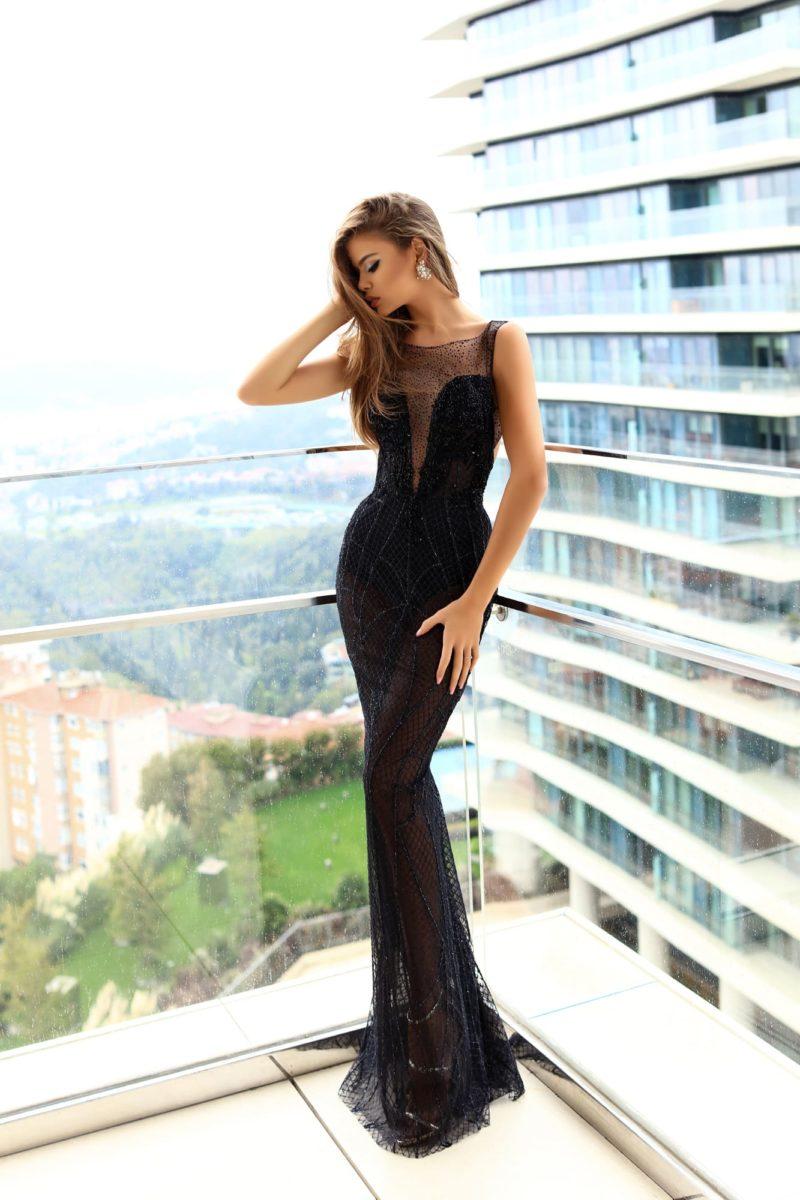 Облегающее вечернее платье черного цвета со стильной полупрозрачной юбкой.