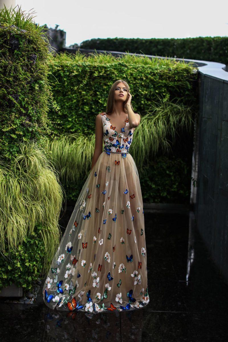 Оригинальное вечернее платье бежевого цвета с отделкой разноцветными бабочками.
