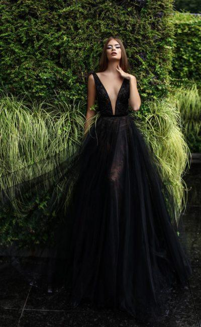 Драматичное вечернее платье черного цвета с глубоким V-образным вырезом.