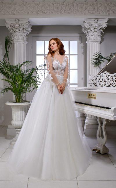 Свадебное платье с воздушной юбкой и полупрозрачным верхом с рукавом.