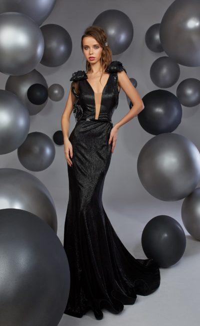 Черное вечернее платье облегающего кроя с объемной отделкой на плечах.