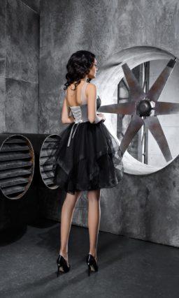 Вечернее платье с открытым лифом и многослойной юбкой до середины бедра.