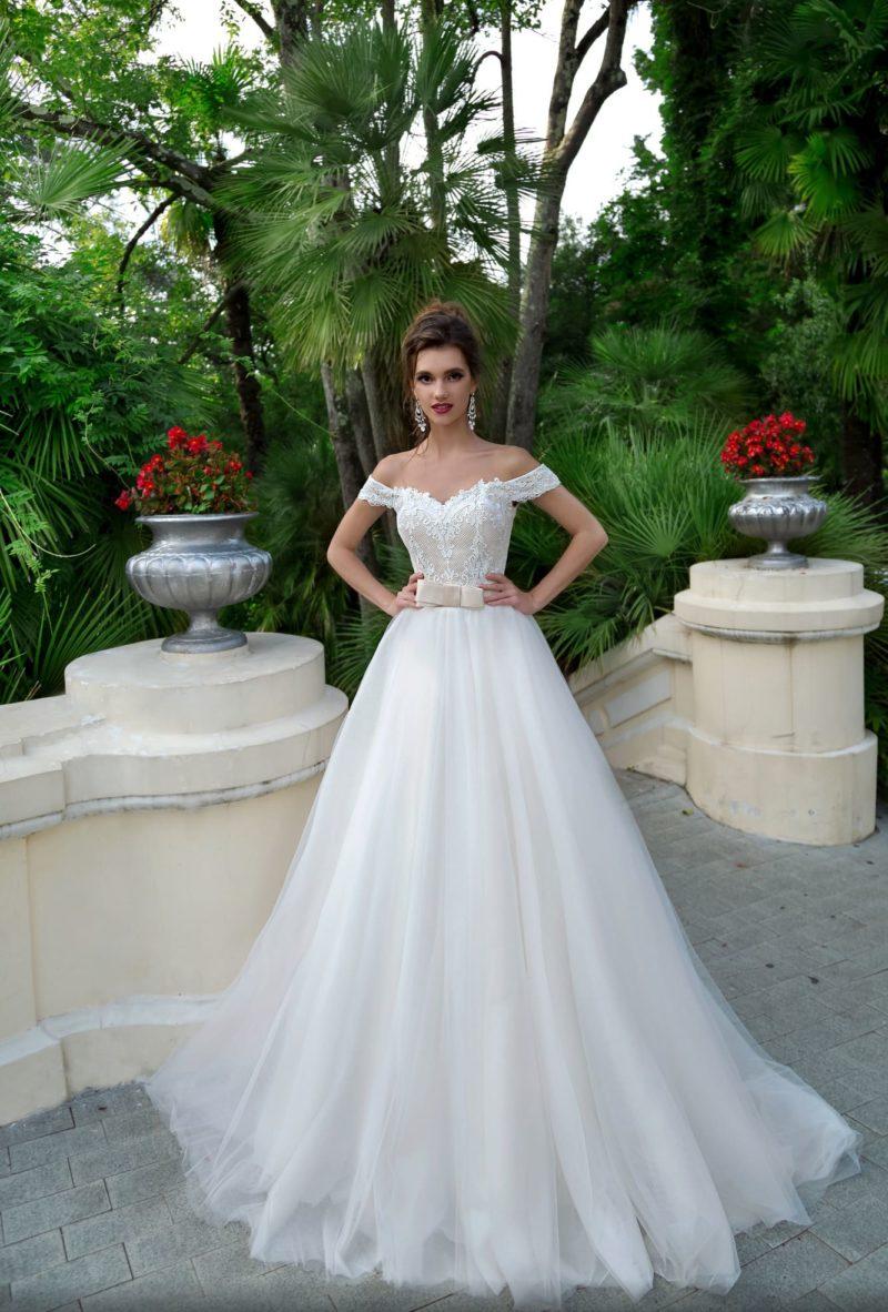 Свадебное платье пышного кроя с широким поясом и бежевым корсетом.