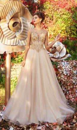 Кремовое вечернее платье с золотистой отделкой и многослойной юбкой.