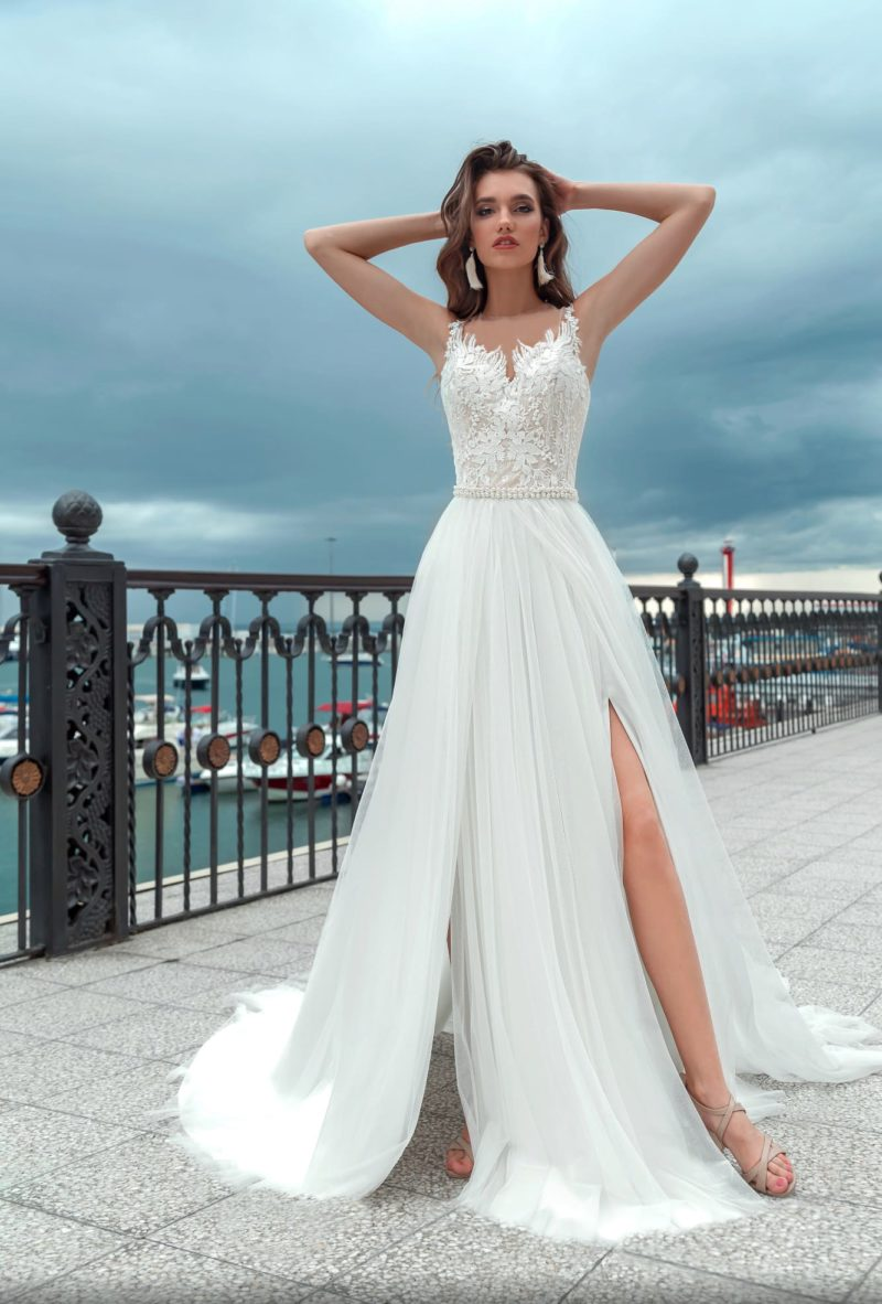 Свадебное платье с вырезом на спинке и многослойной юбкой с разрезами.