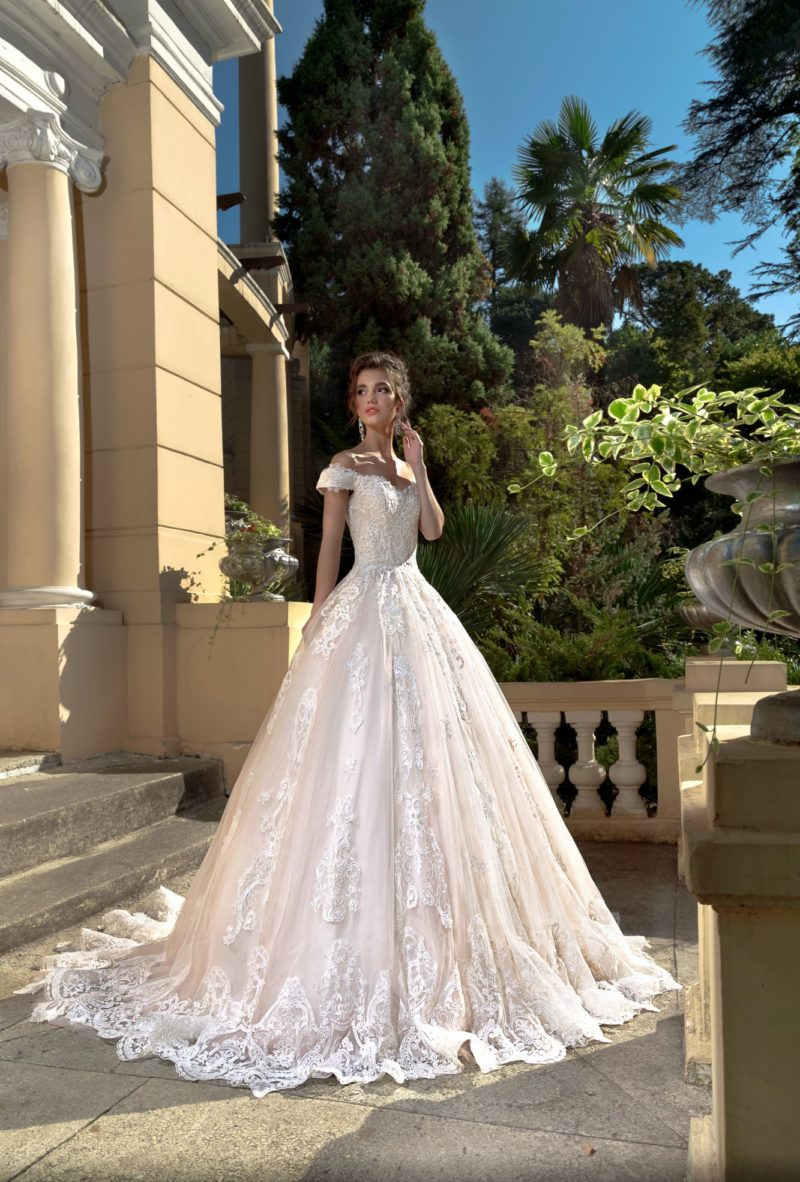 Свадебное платье розового цвета с открытым верхом и пышным силуэтом.