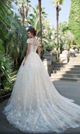 Пышное свадебное платье цвета слоновой кости с коротким рукавом.