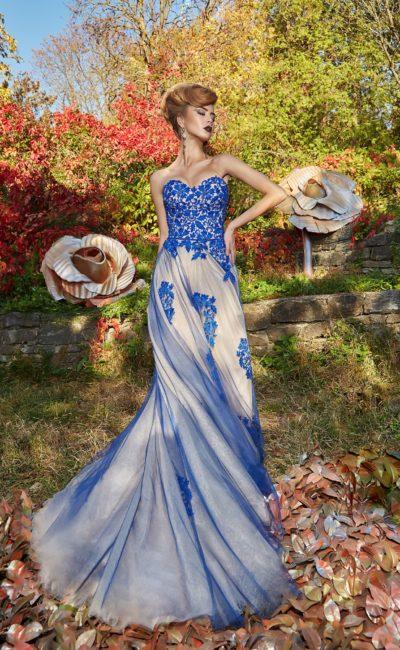 Бежевое вечернее платье с голубым декором, с открытым лифом и многослойной юбкой.