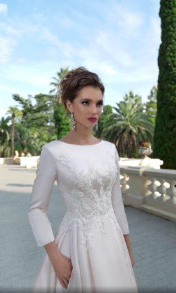 Атласное свадебное платье с закрытым верхом и кружевным декором.