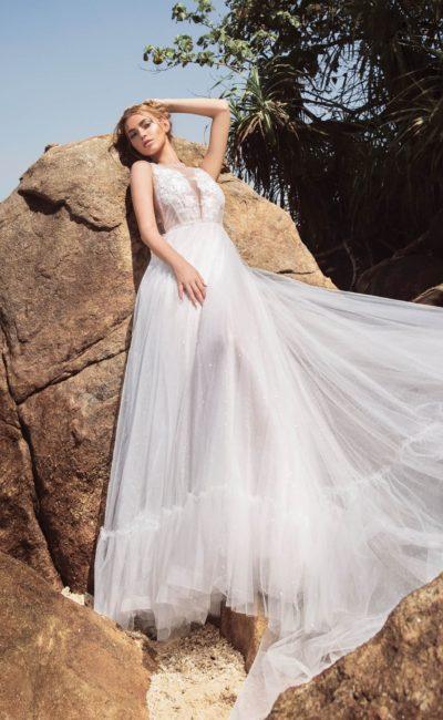 Свадебное платье с оборкой по низу подола и эффектным декольте.